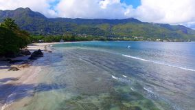 Aerial view of ocean, beach and mountains on the tropical island, Seychelles 6. Drone shot of Beau Vallon Beach, ocean and mountains on the beach of tropical stock video