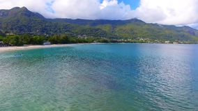 Aerial view of ocean, beach and mountains on the tropical island, Seychelles 5. Drone shot of Beau Vallon Beach, ocean and mountains on the beach of tropical stock video footage