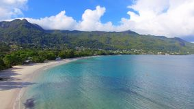 Aerial view of ocean, beach and mountains on the tropical island, Seychelles 1. Drone shot of Beau Vallon Beach, ocean and mountains on the beach of tropical stock footage