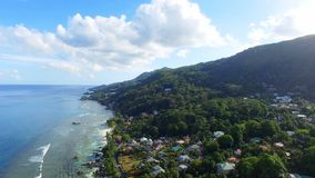 Aerial view of ocean and houses on the beach on tropical island, Seychelles 2. Drone shot of beau vallon beach, ocean and houses on the beach on tropical island stock footage