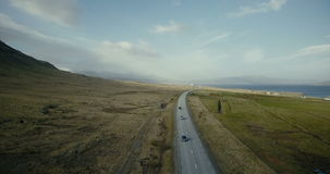 Aerial view of the ocean and mountains valley. Cars riding on the countryside road with field around. stock video footage