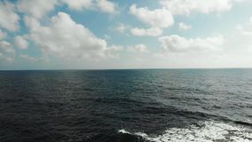 Aerial view of ocean sea horizon with blue sky and clouds. Strong waves hitting rocky beach creating foam and splashing stock video footage