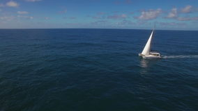 Aerial view of ocean, skyline and sailing yacht. Aerial shot of white yacht sailing in dark blue ocean. Water traveling stock video footage