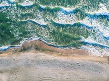 Aerial view of ocean waves crashing on beach. Aerial view of crashing wave in ocean with warm sunset light. Wave crashing on reef. Top view stock photography
