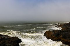 Aerial view of ocean waves and fantastic rocky coast in foggy morning royalty free stock images