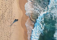 Aerial view of the ocean waves washing on the beach. Top view of man standing on the beach while the ocean wave crushing the coast stock images
