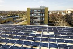 Free Aerial View Of Blue Shiny Solar Photo Voltaic Panels System On Commercial Roof Producing Renewable Clean Energy On City Landscape Stock Photography - 149656322