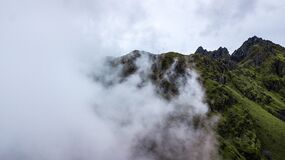 Free Aerial View Of High Green Mountains Rocky Peaks Covered With Fog And Clouds Stock Images - 179466794