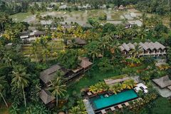Free Aerial View Of Luxury Hotel With Straw Roof Villas And Pools In Tropical Jungle And Palm Trees. Luxurious Villa, Pavilion In Royalty Free Stock Photography - 184254707