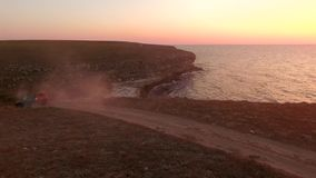 AERIAL VIEW. Offroader Car Driving. AERIAL VIEW. This is an aerial view of black offroader car driving to the beach along Tarkhankut coast in Crimea at sunset stock footage