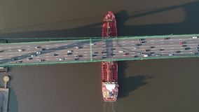 Aerial View of Oil Tanker Ship Passing Under a Suspension Bridge Full of Cars.  stock video footage