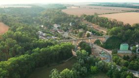 Aerial View of Old Bridge Viaduct in Green Wood Near The Village. Railroad Over Valley. stock video footage