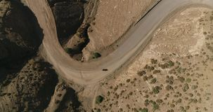 Aerial view of old motorcycle driving on country road in mountain. Cinematic drone shot flying over gravel road stock video footage