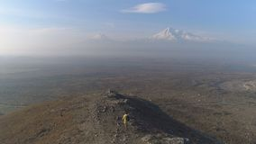 Aerial view: one man walking on the fog mountain. Backview aero shot: guy motion on the way to the peak and looking at cloudy skyline. Armenian Ararat in autumn stock footage