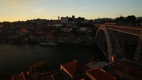 Porto Bridge train. Aerial view of Oporto skyline and Ribeira Waterfront with metro train crossing Douro River at sunset stock video footage