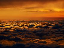 Red cloudscape. Aerial view of orange fluffy flat cloudscape with sun behind the clouds on the background Royalty Free Stock Image