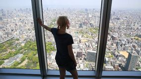 Osaka skyline woman. Aerial view of Osaka skyline in Japan. Travel and tourism asia concept. Young caucasian tourist woman with open arms enjoying Osaka stock footage