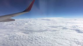 Aerial view out of window of amazing clouds skyline and flying airplane wing - stock video footage