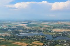 Aerial view over agricultural fields near Bucharest, Romania. Aerial view over a river and the surrounding houses and agricultural fields near Bucharest, Romania Royalty Free Stock Image