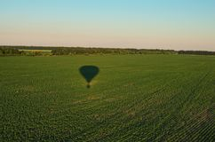 Aerial view over the agricultural fields on a sunny summer day. Air balloon shadow on the green plants. Kyiv region, Ukraine.  royalty free stock photo