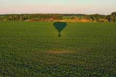 Aerial view over the agricultural fields on a sunny summer day. Air balloon shadow on the green plants. Kyiv region, Ukraine.  stock images