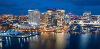 Aerial View Over Baltimore Downtown City Skyline Inner Harbor. The buildings are illuminated in the downtown urban core of Baltimore Maryland stock image
