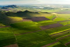 Aerial view over a beautiful scene with green fields, lakes and mountains at golden hour in the spring Royalty Free Stock Images