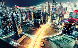 Aerial view over a big futuristic city by night. Business bay, Dubai, United Arab Emirates. Nighttime skyline. Vintage effect Stock Images