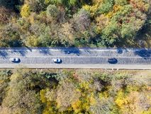 Aerial view over car travelling through colorful forest royalty free stock image