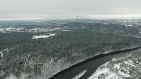Aerial view over the city near river and forest winter stock video