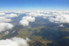 Aerial view over the cumulus clouds and ground. Royalty Free Stock Image