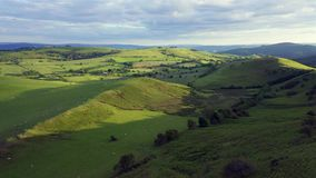 Aerial View over Green Countryside Hills. Aerial view over green hills of countryside fields in soft warm sunset light. Shropshire in United Kingdom stock video