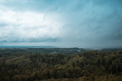 Aerial view over the green forest in evening. Cloudy mystery. Landscapes of Latvia. Stock Photos