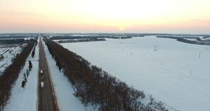 Aerial view over the highway in the winter evening. Aerial shot of cars and trucks driving on a road on winter evening. The road goes into the horizon, the track stock footage