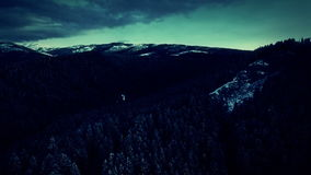 Aerial view over hills and mountains in winter with storm clouds and lightnings stock footage