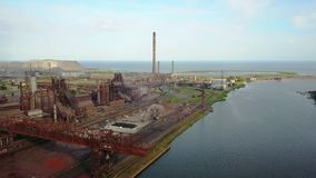 Aerial view over industrialized city with air atmosphere and river water pollution from metallurgical plant near sea stock video footage