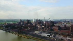 Aerial view over industrialized city with air atmosphere and river water pollution from metallurgical plant near sea stock video