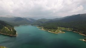 Aerial view over lake and mountains 2. 4K aerial view of the Bolboci Lake. A wonderful trip close to Sinaia one of the highest altitude mountain roads in Romania stock footage