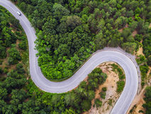 Aerial view over mountain road. Going through forest landscape Royalty Free Stock Photo