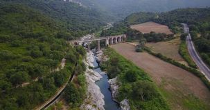 Aerial view over a river and a bridge stock video footage