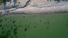 Aerial view over a sand beach and calm clear ocean. Flying over a sand beach on the island of Gotland in Sweden during autumn stock video