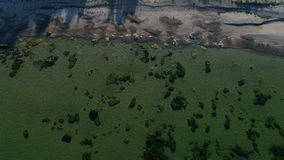Aerial view over a sand beach and calm clear ocean. Flying over a sand beach on the island of Gotland in Sweden during autumn stock video footage