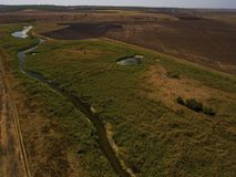 Aerial view over the small river and fields. Stock Photography