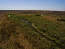 Aerial view over the small river and fields. Stock Images