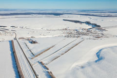 Aerial view over snowy field and road Stock Photos