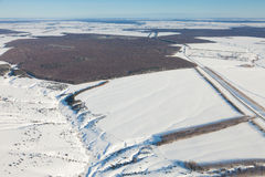 Aerial view over snowy field and road Stock Photo