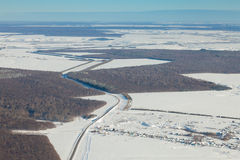 Aerial view over snowy field and road Royalty Free Stock Photos