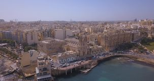 Aerial view over Spinola Bay. With Traditional maltese Luzzu fishing boats and beautiful view from above with St Julian, Sliema and Valetta cities stock footage