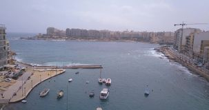 Aerial view over Spinola Bay. With Traditional maltese Luzzu fishing boats and beautiful view from above with St Julian, Sliema and Valetta cities stock video