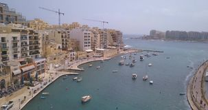 Aerial view over Spinola Bay. With Traditional maltese Luzzu fishing boats and beautiful view from above with St Julian, Sliema and Valetta cities stock video footage